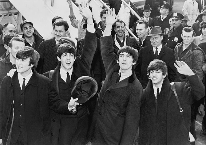 The Beatles wave to fans after arriving at Kennedy Airport. (Photo credit: Wikipedia)
