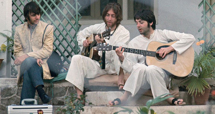 Ringo watches intently as John and Paul work on a song with their acoustic guitars while in India in February of 1968.