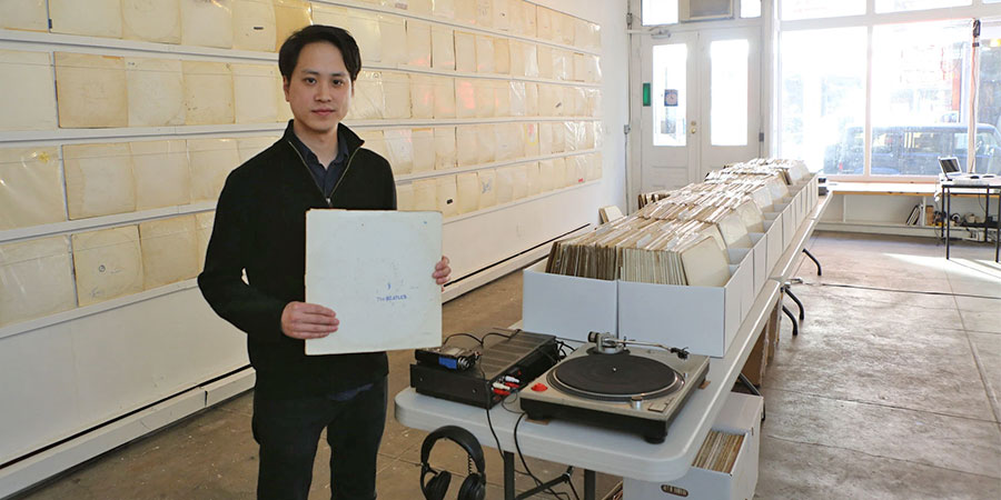 "The artist Rutherford Chang at his installation ""We Buy White Albums"" at Recess Gallery. (Photo: Chester Higgins Jr.)"